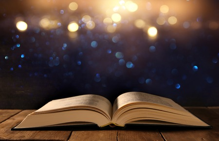 image of open antique book on wooden table with glitter background