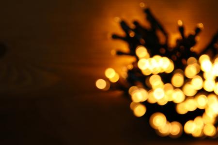 metalic texture: glitter garland lights background. gold and black. de-focused