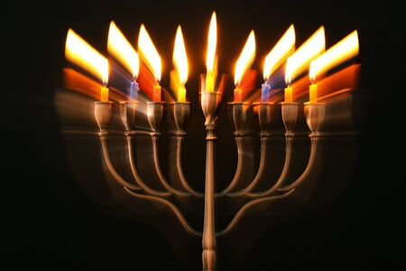 abstract image of jewish holiday Hanukkah background with menorah (traditional candelabra) and burning candles