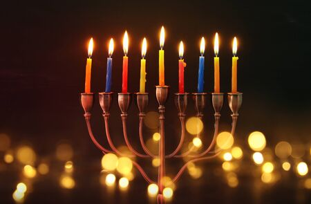 image of jewish holiday Hanukkah background with menorah (traditional candelabra) and burning candles. glitter overlay Stock Photo
