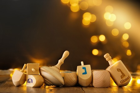 Image of jewish holiday Hanukkah with wooden dreidels colection (spinning top) and gold garland lights on the table Stockfoto