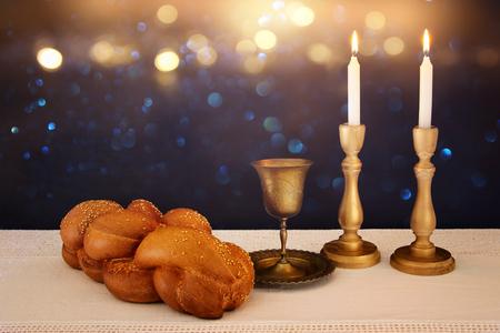 shabat: imagen shabbat pan de jalá, vino shabat y velas sobre la mesa.