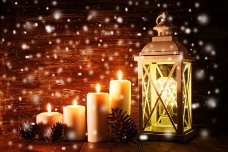 Vintage Lantern with burning candles and pine cones on wooden table. Snow overlay Stock Photo