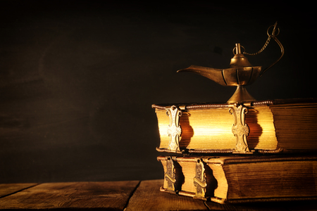 Image of magical aladdin lamp and old books. Lamp of wishes Stock Photo