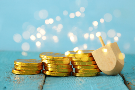 jewish holiday Hanukkah image background with traditional spinnig top and chocolate coins. Glitter overlay