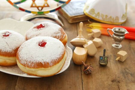 image of jewish holiday Hanukkah background with traditional spinnig top, doughnuts and menorah (traditional candelabra) Stock Photo