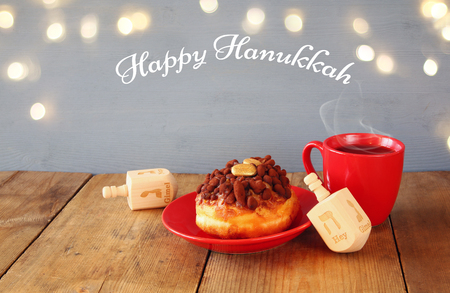 image of jewish holiday Hanukkah with donuts, wooden spinning top and cup of hot chocolate.