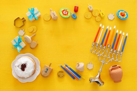 Top view image of jewish holiday Hanukkah background with traditional spinnig top, menorah (traditional candelabra) and burning candles Stock Photo