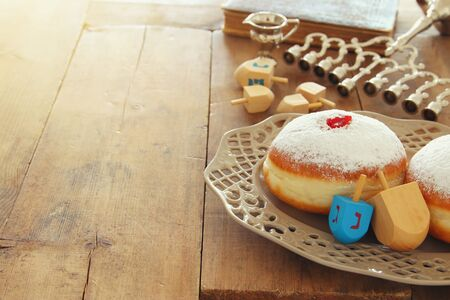 image of jewish holiday Hanukkah background with traditional spinnig top, doughnuts and menorah (traditional candelabra) Foto de archivo
