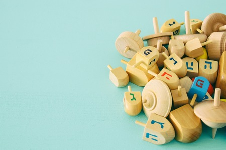 Image of jewish holiday Hanukkah with wooden dreidels colection (spinning top) on the table.