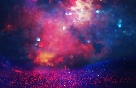 Purple and red glitter lights background. defocused
