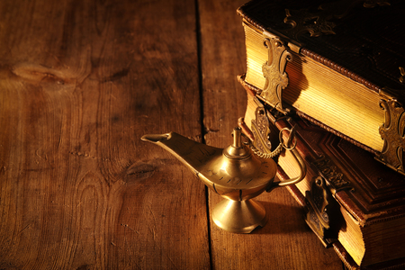 Image of magical genie lamp and old books. Lamp of wishes Stock Photo