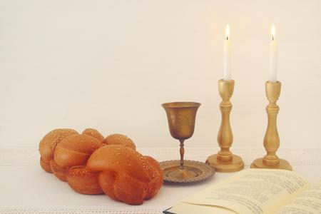 shabbat: shabbat image. challah bread, shabbat wine and candles on the table.