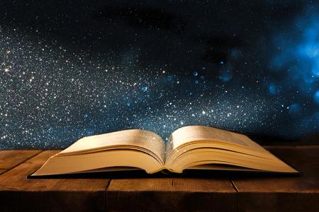 Bild des offenen antiken Buches auf Holztisch mit Glitzer-Overlay Standard-Bild - 89215311