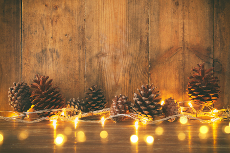 Holiday image with Christmas golden garland lights and pine cones over wooden background.