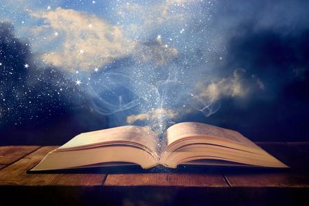 Immagine del libro antico aperto sul tavolo in legno con sovrapposizione di glitter Archivio Fotografico - 89971836