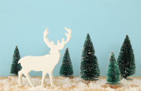 Immagine di alberi di Natale e renne sul tavolo in legno nevoso.