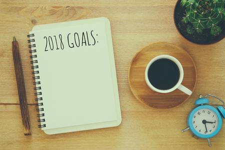 ノートブック、木製の机の上のコーヒー カップを持つ上面 2018 目標一覧