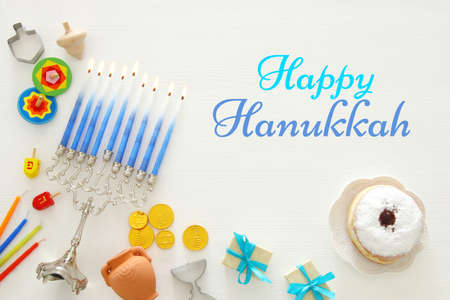 Top view image of jewish holiday Hanukkah background with traditional spinnig top, menorah (traditional candelabra) and burning candles Foto de archivo