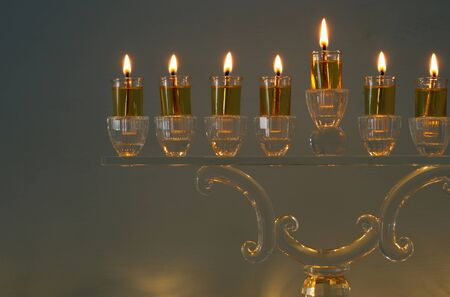 image of jewish holiday Hanukkah background with traditional spinnig top, doughnuts and menorah (traditional candelabra) Archivio Fotografico