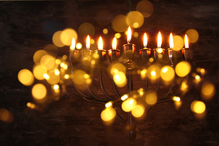 Low key image of jewish holiday Hanukkah background with menorah (traditional candelabra) and burning candles.