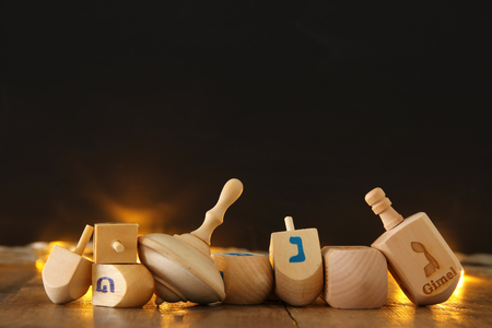 trompo de madera: Image of jewish holiday Hanukkah with wooden dreidels colection (spinning top) and gold garland lights on the table Foto de archivo