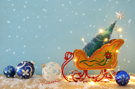 Image of christmas tree on the wooden old sled over snowy wooden table 스톡 콘텐츠