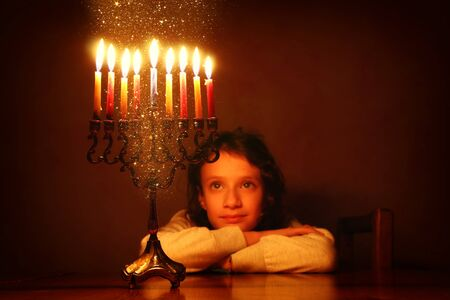 Low key image of jewish holiday Hanukkah background with cute girl looking at menorah (traditional candelabra) and burning candles