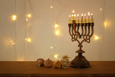 Low key image of jewish holiday Hanukkah background with traditional spinnig top, menorah (traditional candelabra) and burning candles