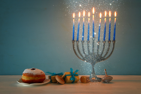 mage of jewish holiday Hanukkah background with traditional spinnig top, menorah (traditional candelabra) and burning candles Stock Photo