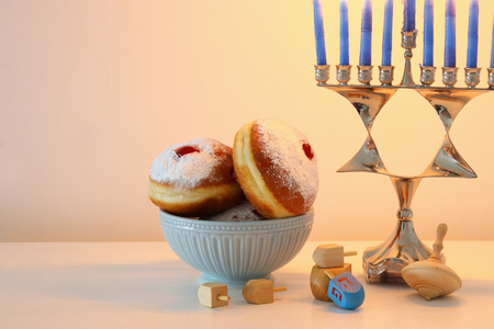 image of jewish holiday Hanukkah background with traditional spinnig top, menorah (traditional candelabra) and donut Foto de archivo