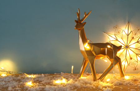 Gold shiny reindeer on snowy wooden table with christmas garland lights