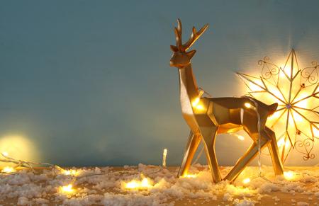 Złoty błyszczący renifer na śnieżnym drewnianym stole z lampkami choinkowymi