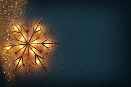 Image of christmas shining star over wooden background Фото со стока