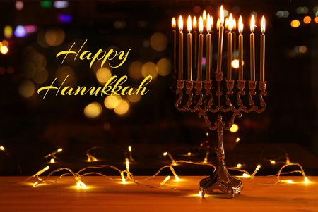 image of jewish holiday Hanukkah background with menorah (traditional candelabra) and burning candles in front of the window Stock Photo