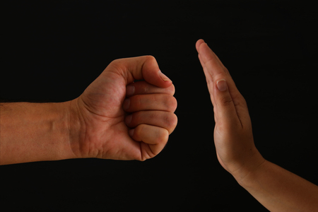 Image of male fist and female hand showing STOP. Domestic violence concept against women
