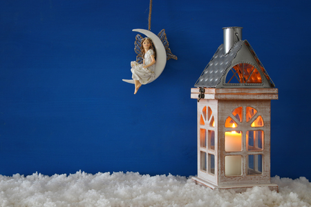Wooden old house with candle and fairy on the moon over the snow and blue nackground