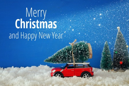 Red car carrying a christmas tree over the snow 스톡 콘텐츠