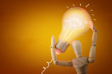 Wooden dummy holding shiny light bulb. New idea concept or choosing the right solution