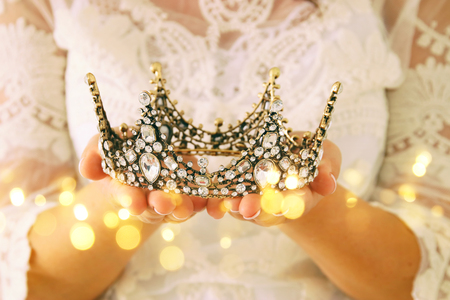 image of beautiful lady with white lace dress holding diamond crown. fantasy medieval period Stock Photo