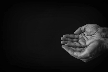 black and white image of open male hand begging for help