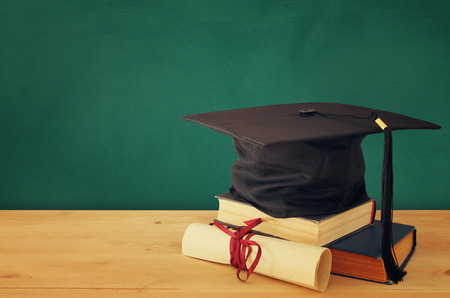 Image of graduation black hat over old books next to graduation on wooden desk. Education and back to school concept Stock Photo