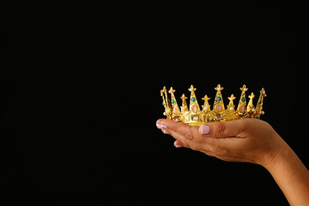 Woman's hand holding a crown for show victory or winning first place over black background Foto de archivo