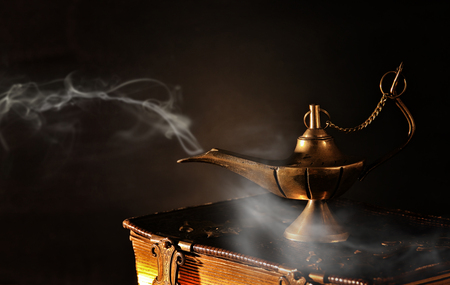 Image of magical aladdin lamp on old books. Lamp of wishes. Stock Photo