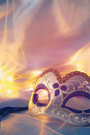 Image of delicate elegant venetian mask over blue silk and tulle fabric background