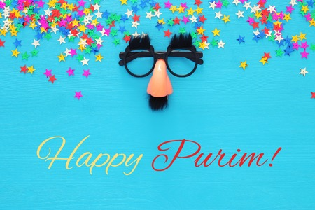 Purim celebration concept (jewish carnival holiday) with funny mustache glasses. Top view. Stock Photo