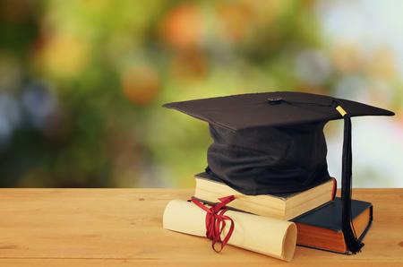 Bild des schwarzen Hutes der Staffelung über alten Büchern nahe bei Staffelung auf hölzernem Schreibtisch. Bildung und zurück zum Schulkonzept Standard-Bild
