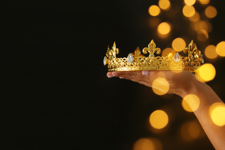 Woman's hand holding a crown for show victory or winning first place over black background with glitter overlay Standard-Bild