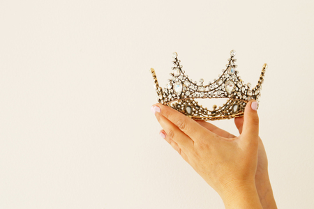 Woman's hand holding a crown for show victory or winning first place. White background. Copy space. Isolated
