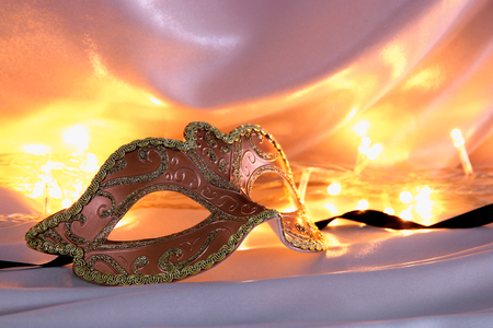 Image of elegant venetian mask over gold silk background Stock Photo